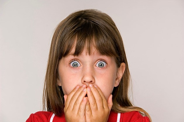 Scared six year old girl with hands covering mouth.
